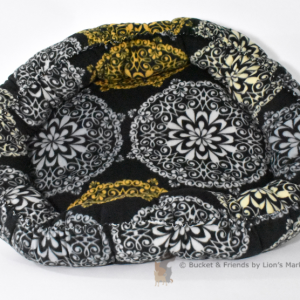 Warm snugly fleece dog bed. Size medium. Black with gray white and yellow medallions.